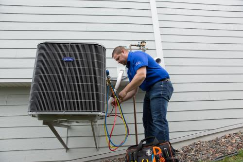 man working on air conditioning unit outside home